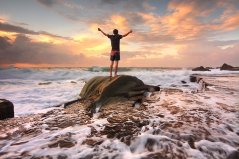 Teen boy stands on a rock among turbulent ocean seas and fast flowing water at sunrise. Worship praise zest adenture solitude finding peace among lifes turbulent times. Overcoming adversity. Motion in water