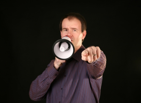 a man makes his demands known by speaking loudly through a megaphone and pointing his finger directly at YOU THE VIEWER with focus on his finger and hand